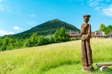 Vlkolinec, Ruzomberok / Slovakia - June 17, 2018: Wooden statue of a villager in the mountain village of Vlkolinec, included in the UNESCO World Heritage.
