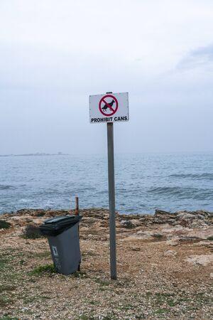 """""""Proibire lattine"""", cani vietati in lingua catalana, firmare in una baia, in un'area protetta di Sa Rápita a Maiorca, Isole Baleari. Cassonetto di riciclaggio sul lato."""