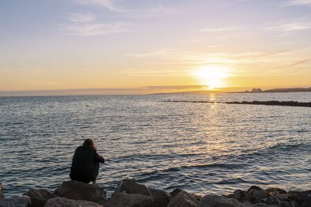 Sea landscape from a beach in the promenada of Palma city, Majorca. A girl sitting on the rocks on her back, watching the sunset in meditation pose