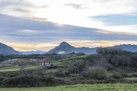 Beautiful landscape at sunset in Principado de Asturias, Spain, Picos de Europa region, near Ribadesella, with a majestic mountain peak silhouette on the background.