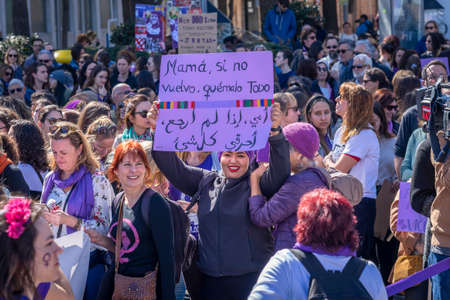 Palma de Mallorca, Spain - March 08, 2020: International Women's Day. Young arabic girl holding a feminist banner in the middle of the crowd. 新聞圖片