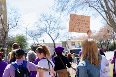 Palma de Mallorca, Spain - March 08, 2020: International Women's Day. Blonde girl with a banner in the feminist protest, in the banner: El 80% DE LAS PERSONAS DESPLAZADAS POR EL CAMBIO CLIMATICO SON MUJERES. 新聞圖片