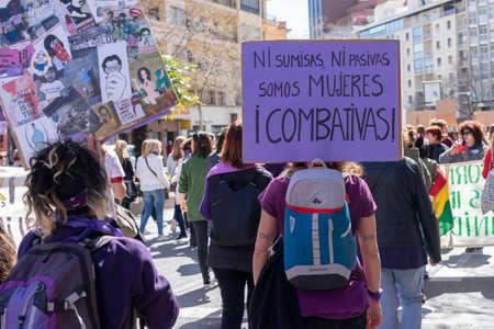Palma de Mallorca, Spain - March 08, 2020: International Women's Day. Young backwards girl in a protest, in the banner: NI SUMISAS NI PASIVAS, SOMOS MUJERES COMBATIVAS.