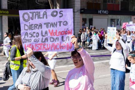 Palma de Mallorca, Spain - March 08, 2020: International Women's Day. Young girls in a protest holding a banner where it puts: OJALA OS DIERA TANTO ASCO LA VIOLACION COMO LA MENSTRUACION. 新聞圖片