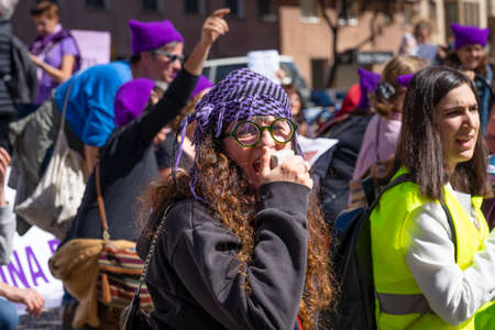Palma de Mallorca, Spain - March 08, 2020: International Women's Day. Woman with a kufiya talking on megaphone at the feminist protest,