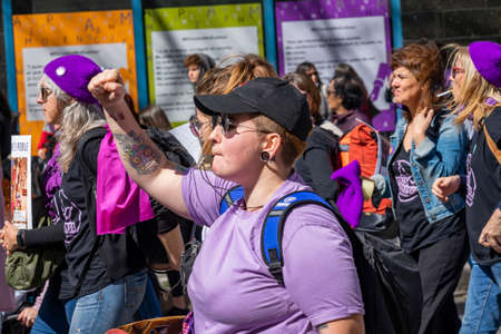 Palma de Mallorca, Spain - March 08, 2020: International Women's Day. Tattoed girl with a whistle and a cap, whit high fist, in the 8m feminist protest.