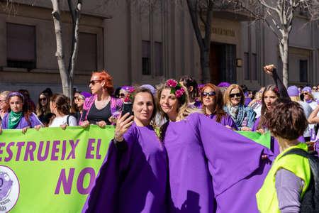 Palma de Mallorca, Spain - March 08, 2020: International Women's Day. Two purple dressed women taking a selfie in the feminist protest.