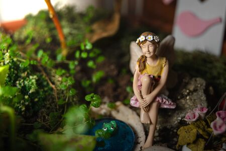 Beautiful decorative miniature fairy for garden or pot, in a small idyllic and fantasy garden