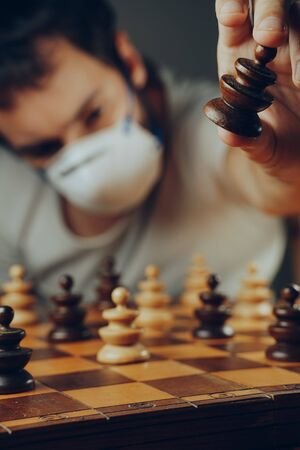 Social distancing in the 2019-ncov or coronavirus crisis. A man in a medical mask moves a token on a chess board full of pawns