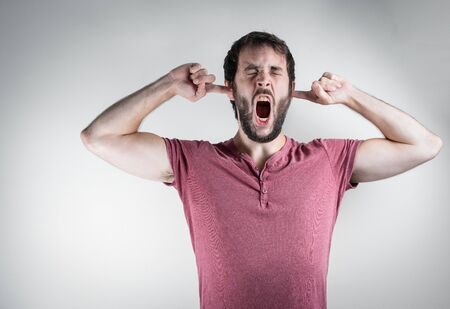 Hombre joven con barba with a grimace of suffering, screaming while covering his ears. Mental health, stress and anxiety mood. On a white background. Stok Fotoğraf
