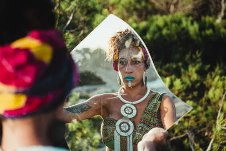 Woman in wild nature, with African face paint and ethnic clothes looking at the mirror