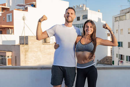 Young couple of athletes posing together and smiling, during a fitness session on their terrace Banque d'images