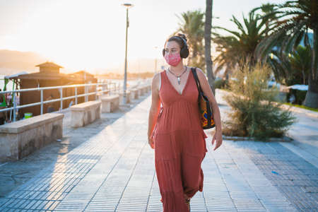 Elegant and beautiful woman wearing ethnic red dress, a fashion medical face mask and headphones, walking along the promenade of Mallorca