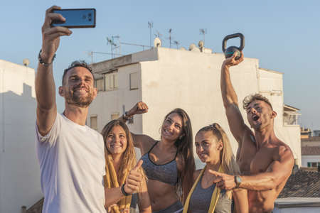 Group of young friends taking a selfie, smiling and having fun after a fitness session on the roof of the building