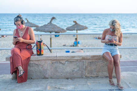 Two women sitting on a stone bench on a promenade with the beach and the sea in the background, maintaining social distance to stop the Coronavirus during the health crisis