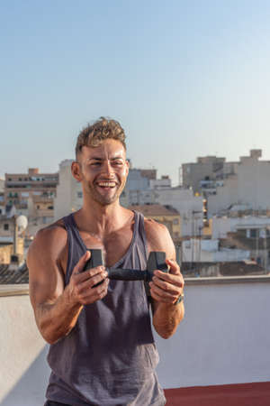 Handsome and athletic man holding a dumbbell in a fitness session, while smiling happily