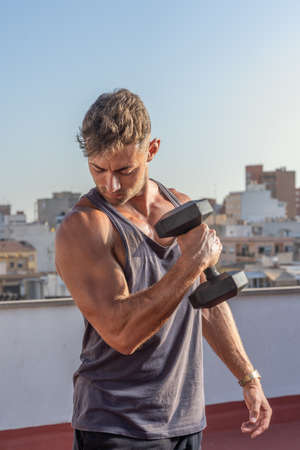 Handsome and athletic man doing weightlifting exercises with a dumbbell in his home terrace