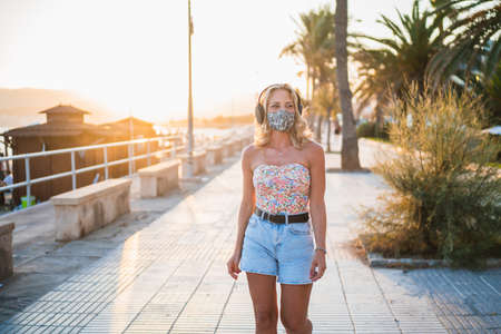 Attractive blonde woman with headphones and protective mask walking with cheerful attitude along the city promenade Banque d'images