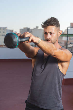 Athletic man doing kettlebell weightlifting exercises on his terrace