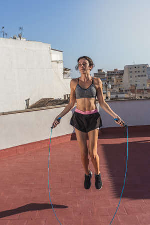 Young woman skipping rope and doing physical training on the terrace of the building, in an urban setting
