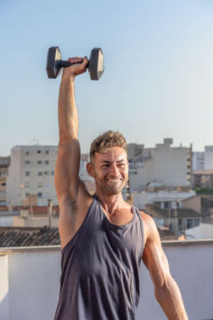 Handsome and athletic man in fitness sesion, lifting dumbbell with arm raised, on his home terrace Banque d'images