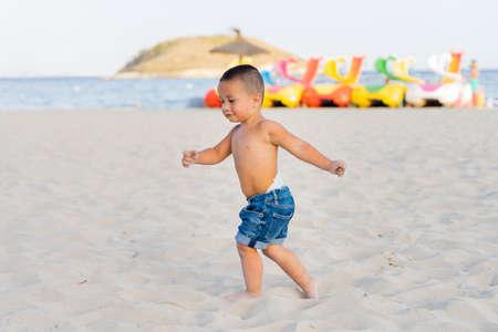Hispanic little boy having fun and running on Magaluf beach, Mallorca, Spain