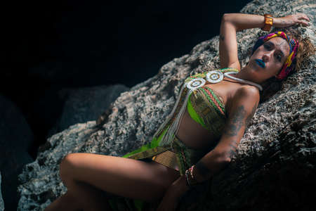 Beautiful woman dressed as Egyptian princess lying on a rock, with a black background