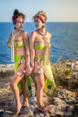 Two beautiful young women with african clothes and makeup, typical of belly dance, looking into each other's eyes while holding hands