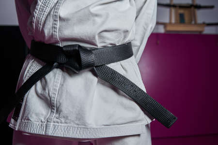 Waist of a man with karate black belt rank, in a martial arts hall