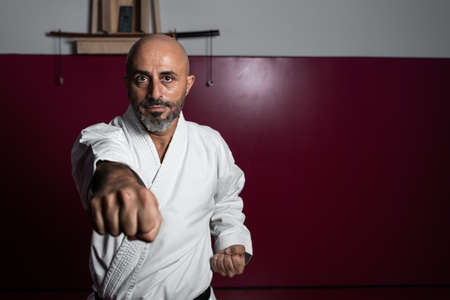 Karate master with focused hand and unfocused face, posing with powerful attitude in his dojo or karate school