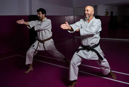 Karate master and his apprentice practicing martial arts attack in their dojo Banque d'images