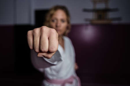 Powerful woman during the coronavirus crisis karate pose giving a punch. Pink background with shadows