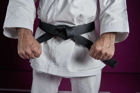 Waist of a karate master with black belt rank, posing with clenched fists as a martial arts salute before a fight