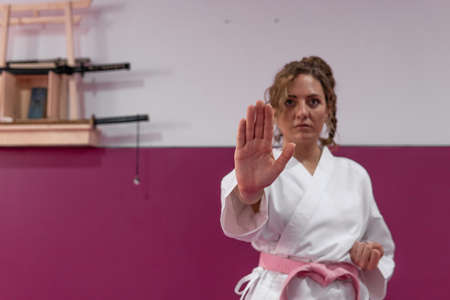 Hand of a female karate fighter practicing martial arts in her dojo, in stop sign