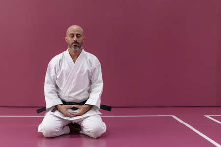 Karate master sitting in meditation pose, back turned, in his dojo or martial arts school