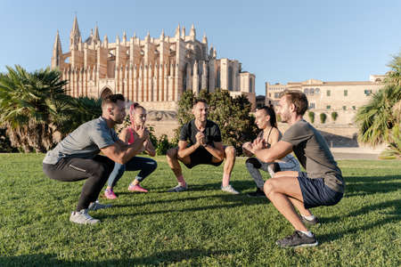 Group of sporty friends doing squat exercise and having fun at outdoor fitness session in city park Banque d'images