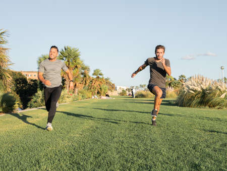 Two young sporty boys competing in a running race, on the grass of the park