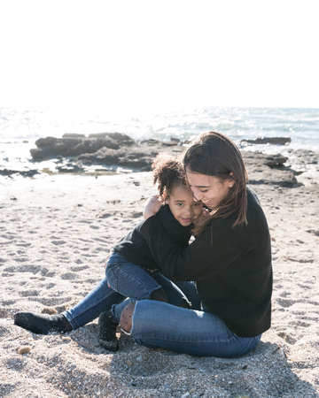 Affectionate kiss between a young mother and her African American daughter, in the sand on the beach