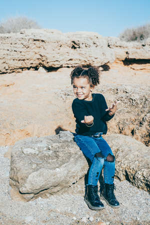 Afro American girl dressed in urban clothing, posing happily and having fun in rocky natural setting