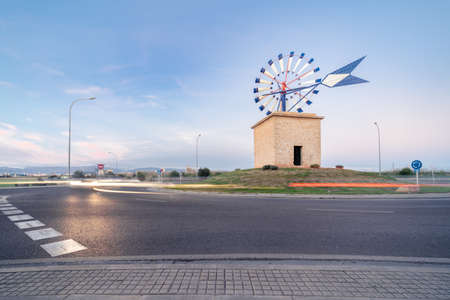 Palma, Majorca, Spain - January 16, 2021: traditional windmill on a roundabout, urban landscape with car trails