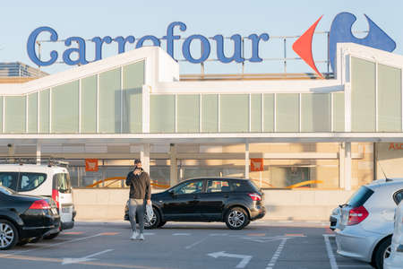 Palma, Majorca, Spain - January 16, 2021: Facade of the Carrefour shopping center, from the parking lot, where a man with a mask walks during the Coronavirus health crisis Éditoriale