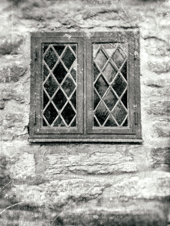 Old front window with leaded windowpane in rough stone wall, textured in black and white tones with scratches and stains. Фото со стока
