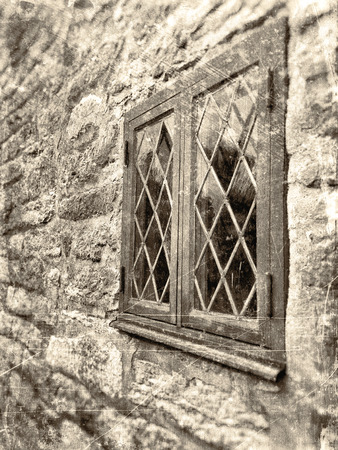 windowpane: Window in angle with leaded windowpane surrounded by a rough stone wall, textured in sepia with scratches and stains. Stock Photo