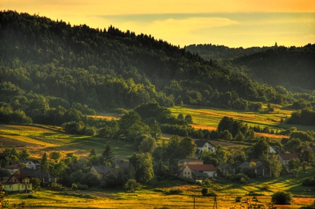 Beautiful evening view of village near hills, Poland photo