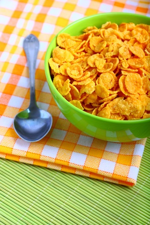 Delicious breakfast corn flakes in green bowl