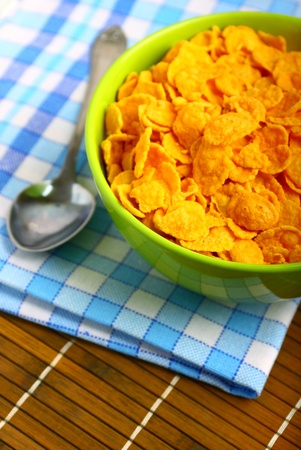 Delicious breakfast corn flakes in green bowl photo