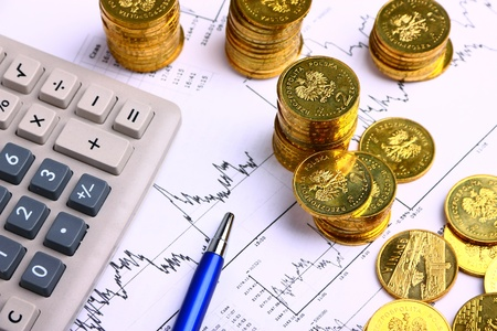 Money coins, calculator on the business stock charts Imagens