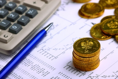 Money coins, calculator on the businness stock charts