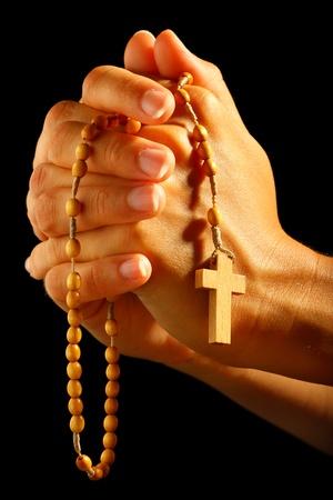 manos orando: Christian humana rezando con el rosario en las manos Foto de archivo