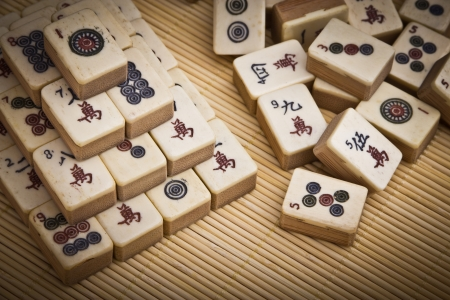 Old chinese game mahjong on bamboo mat background